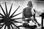 Gandhi at home next to a spinning wheel, which looms in the foreground as a symbol of India's struggle for independence